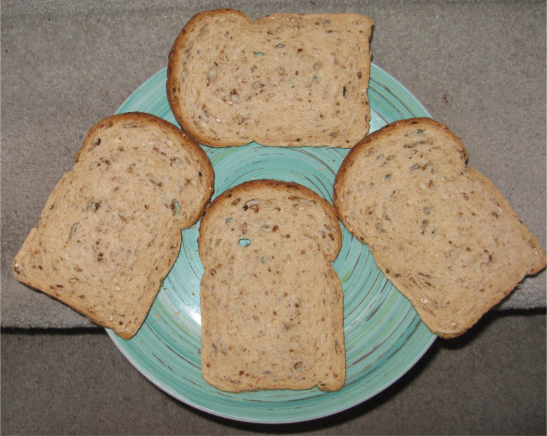 Four slices of brown bread on a blue plate