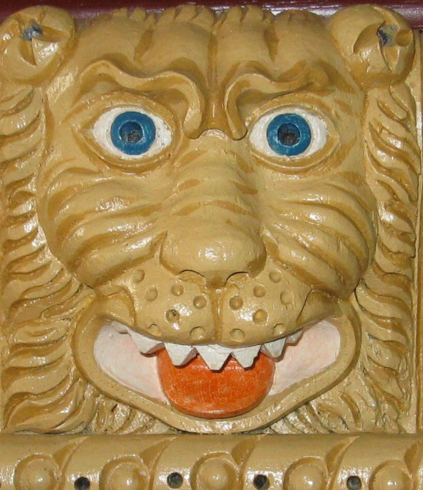 Carved and painted Tudor lion mask dark-yellow face, blue eyes.