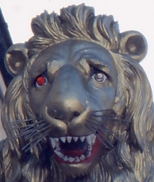 Lion's head carving with one red eye, one normal
