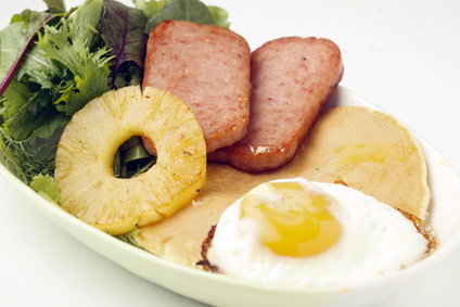 Spam on a plate, incongruously dressed with an elaborate garnish of pineapple, salad and a fried egg