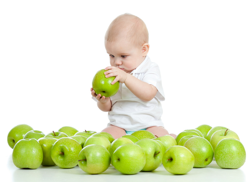 Baby surrounded by green apples, fascinated by the one in his hand